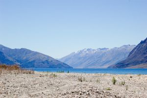 NZ Pebble beach, water, snowcapped mountains by Chunga-Stock