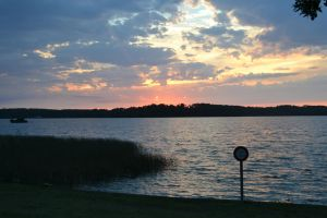 sunset over a lake by cendredelune