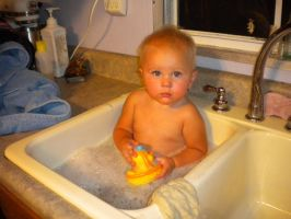Baby taking a bath in kitchen by Huop