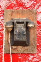 An old telephone on a red wall by feureau