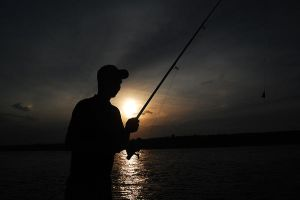 Fisherman at sunset by geographu