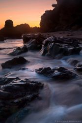 A wave sweeping over the rocks by isotophoto