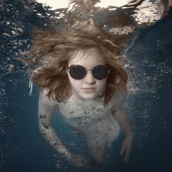 A young girl swims underwater by fly10