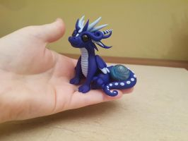 Navy blue dragon with a marble by claymeeples