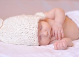 Little baby sleeping on white covered bed by morrowlight