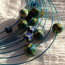 Traditional pottery beads on modern steel by ErrantDreams