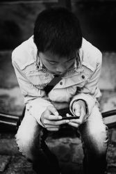 Boy playing with his iPod by MbOscarsson