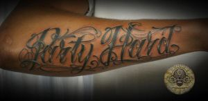 Chicano lettering forearm tat by 2Face-Tattoo