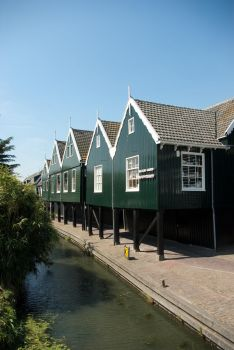 Pole houses along canal by steppeland